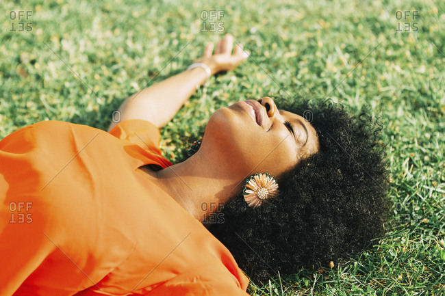 Carefree, serene young woman laying in sunny grass