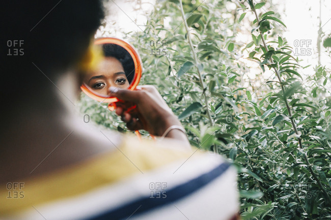 Young woman looking in compact mirror
