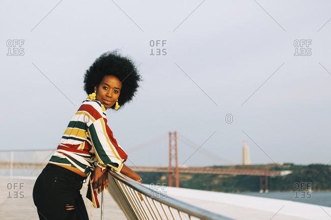 Portrait confident young woman at waterfront with 25 de Abril Bridge in background, Lisbon, Portugal