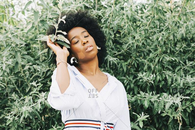 Serene woman standing at green bush