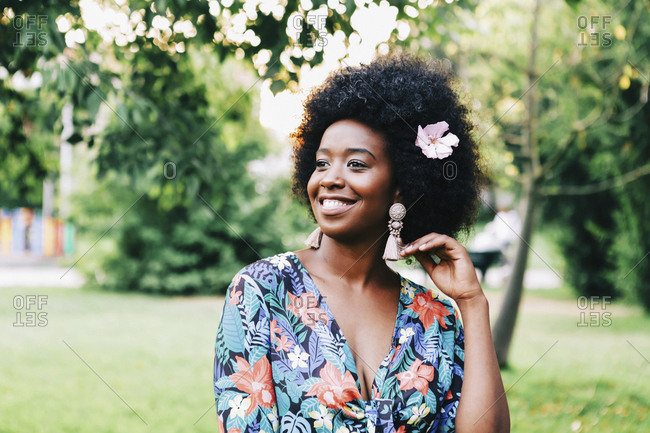 Happy young woman with pink flower in hair