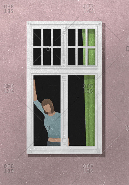 View from outside of woman standing by a window