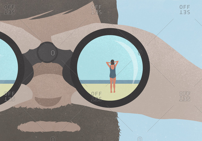 Reflection of woman standing on beach in binoculars held by a man with a beard