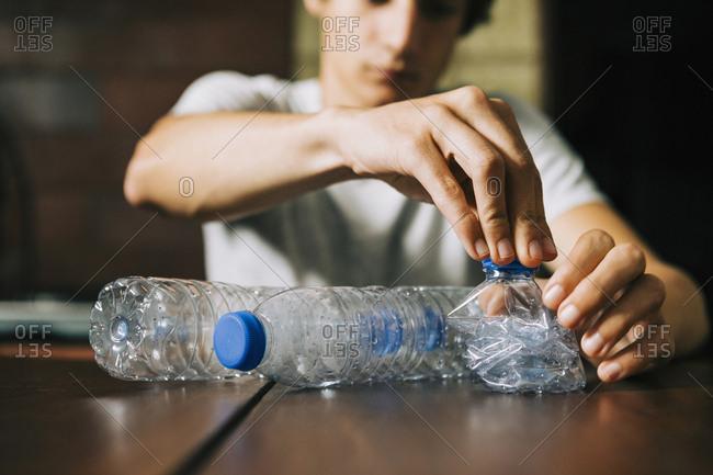 Teenage boy recycling water bottles