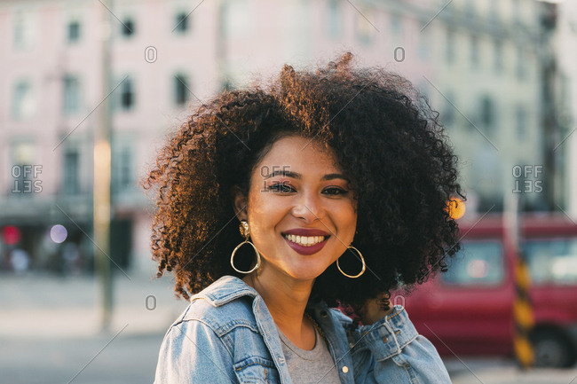 Portrait smiling, confident young woman on urban street