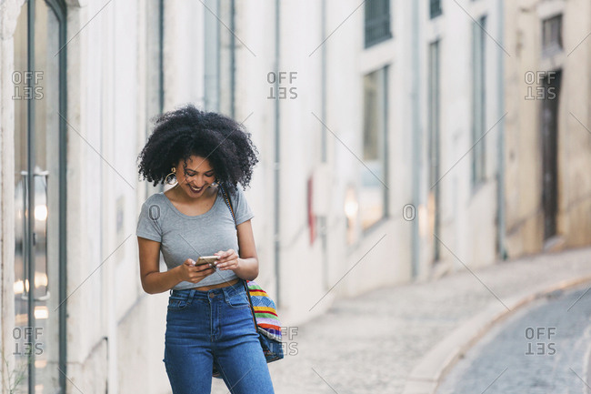 Young woman using smart phone on urban street