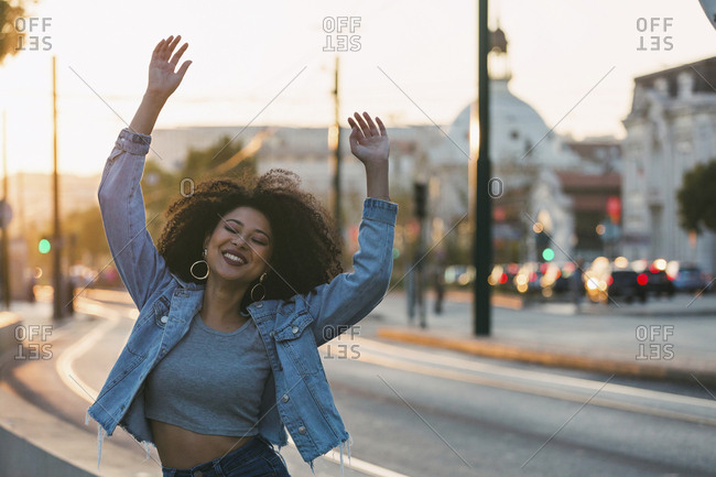 Portrait carefree, exuberant young woman on urban street, Lisbon, Portugal