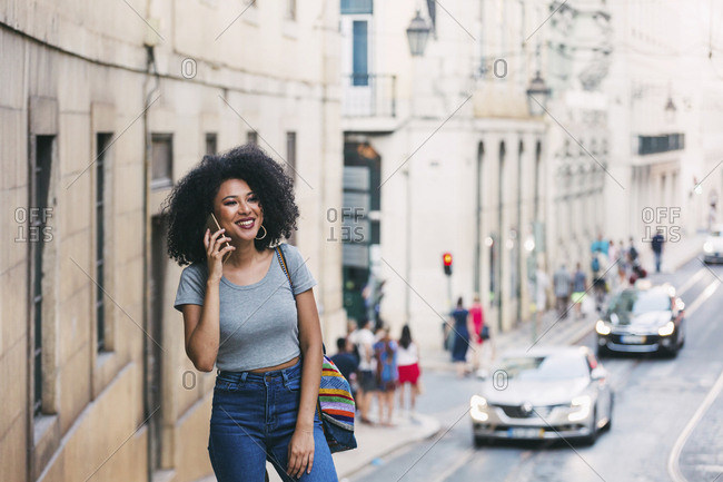 Smiling young woman talking on smart phone on urban street, Lisbon, Portugal