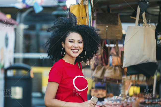 Portrait smiling, confident young woman shopping at market stall