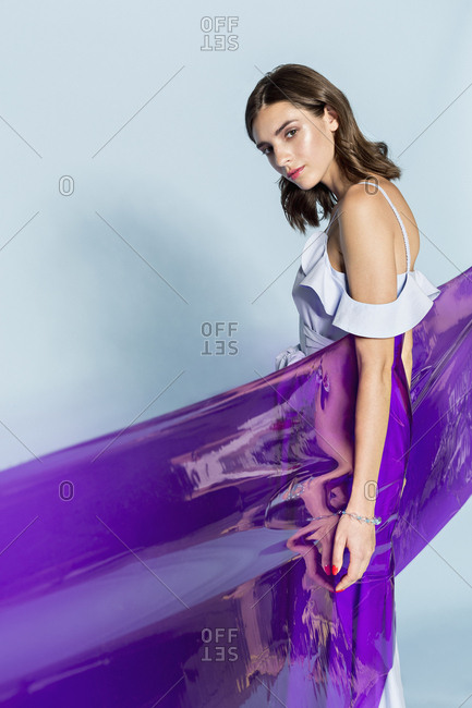 Portrait of a female fashion model wrapped in purple plastic sheet against blue background