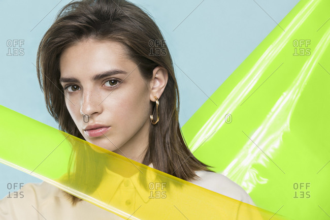 Portrait of a female fashion model posing with yellow plastic sheets