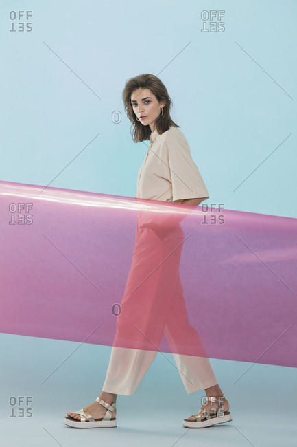 Portrait of a female fashion model posing with pink plastic sheet against blue background