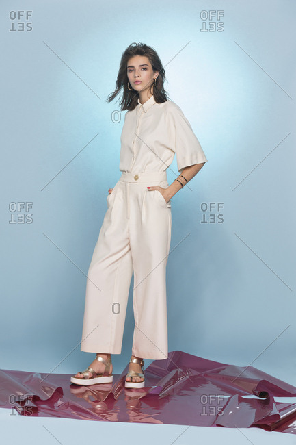Portrait of female fashion model posing against blue background