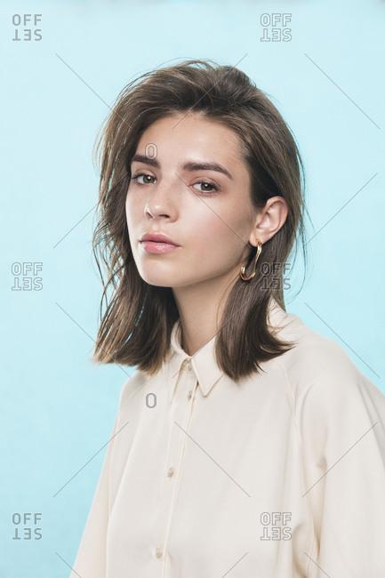 Portrait of female fashion model against blue background