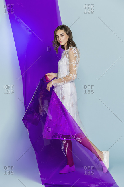 Portrait of a female fashion model posing with purple plastic sheet against blue background