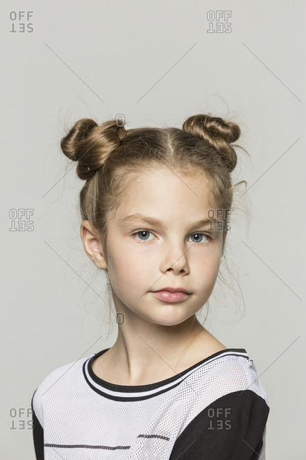 Portrait of young girl with double hair buns against grey background