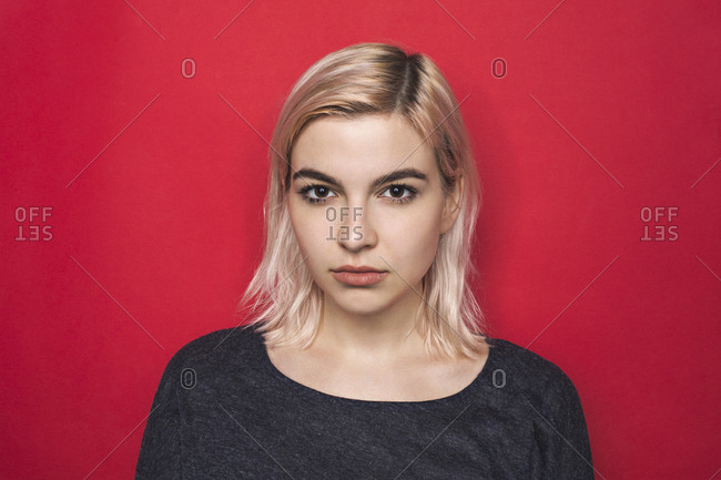 Portrait of woman with bleached hair and serious expression against red background