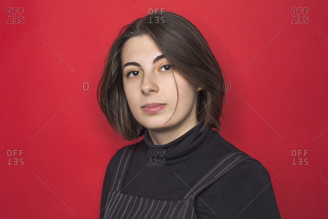 Portrait of woman with dark hair and serious expression against red background