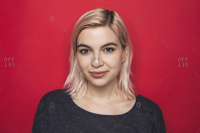 Portrait of woman with bleached hair and smiling against red background