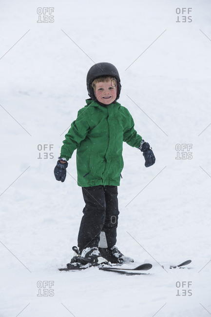 Portrait smiling, cute boy skiing in snow