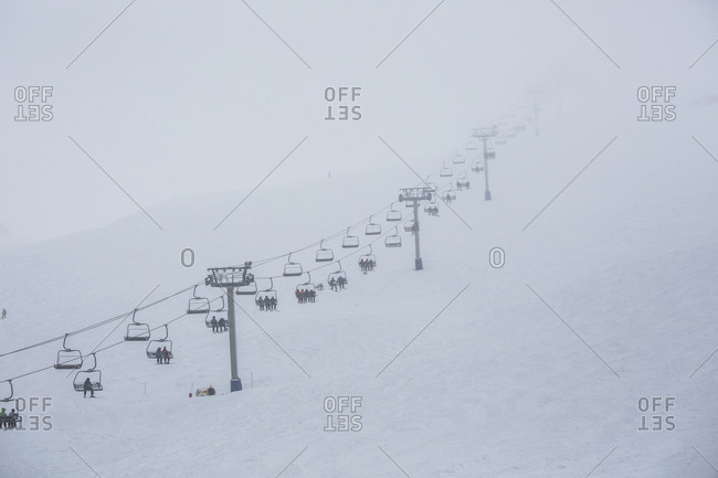 Skiers riding ski resort chair lift up mountainside