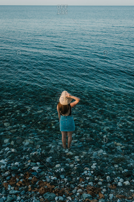 Woman in a jean skirt wearing flaxen hat standing in the water with beautiful seascape view