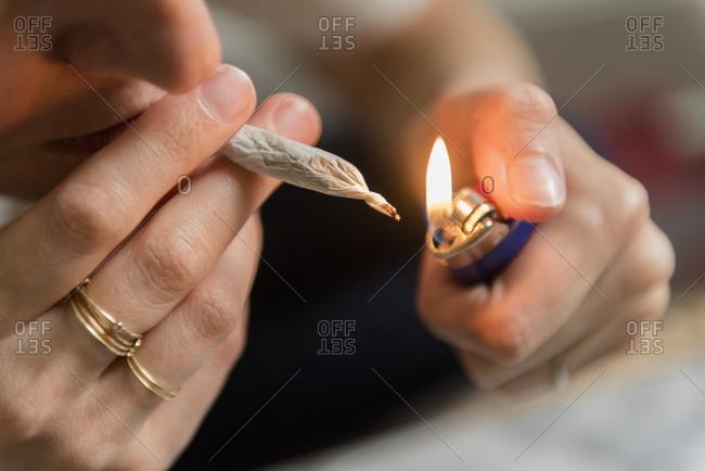Woman lighting marijuana joint
