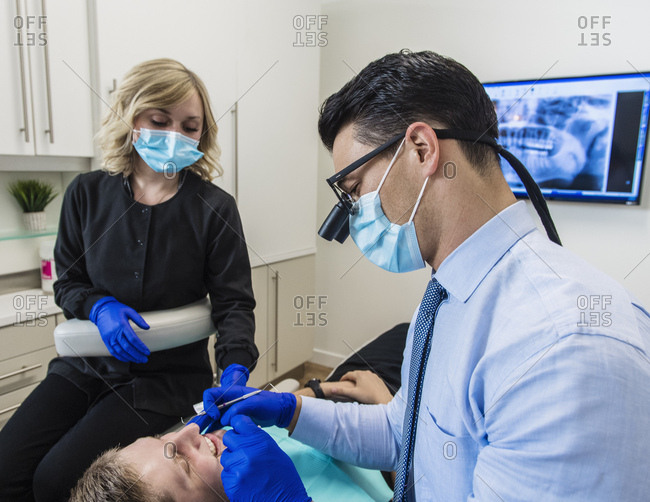 Dentist and dental nurse examining patient's teeth