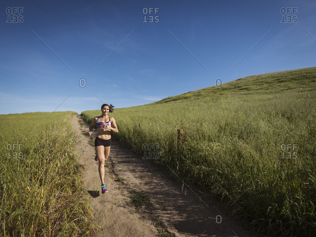 Mid adult woman jogging on path through field