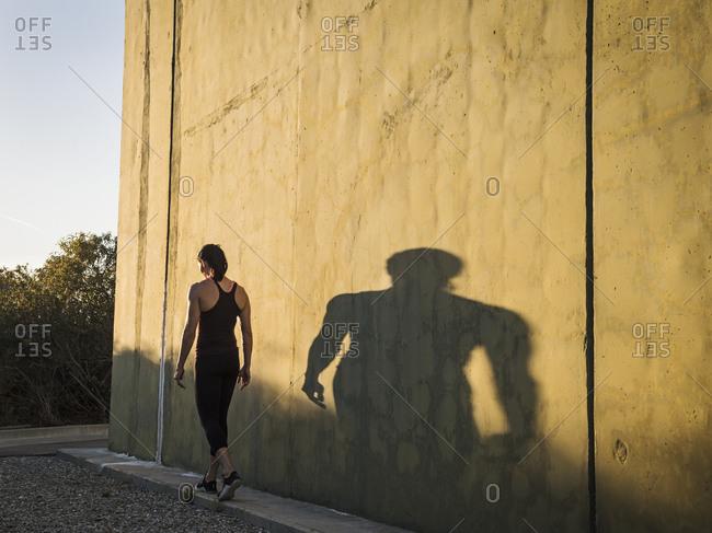 Woman in sportswear walking by concrete wall