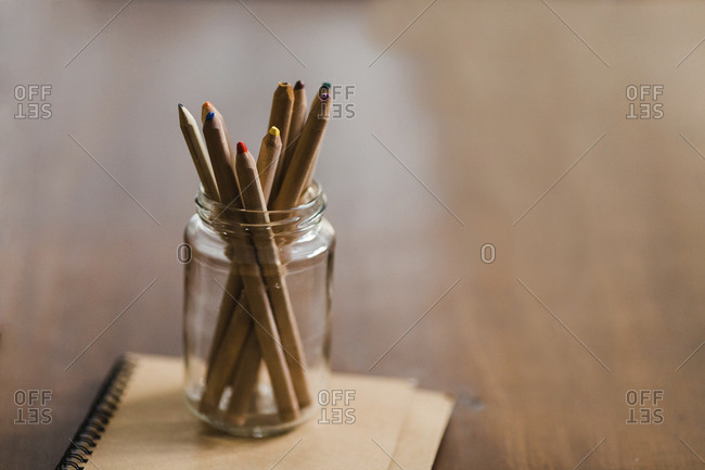 Colored pencils in jar on book