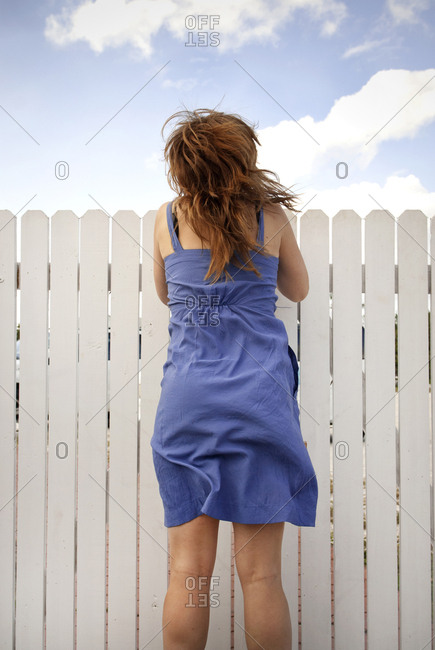 Woman jumping to see over white picket fence