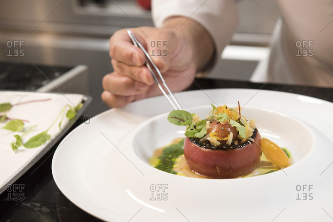 Chef uses tweezers to plate tomato dish