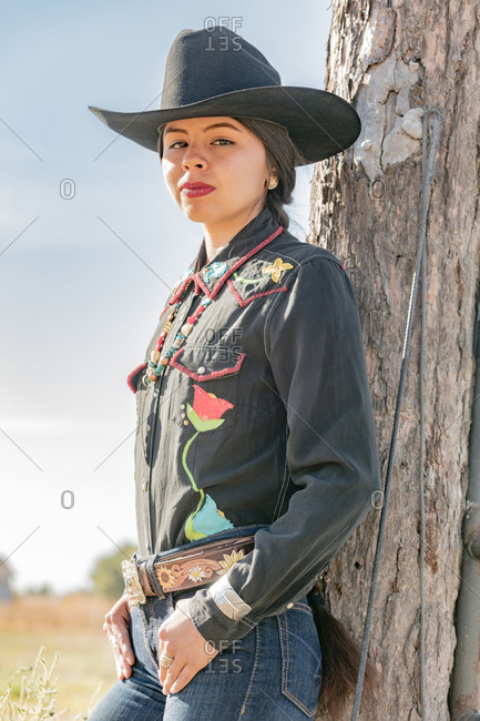Portrait of a Native American young woman wearing western clothing and a cowboy hat