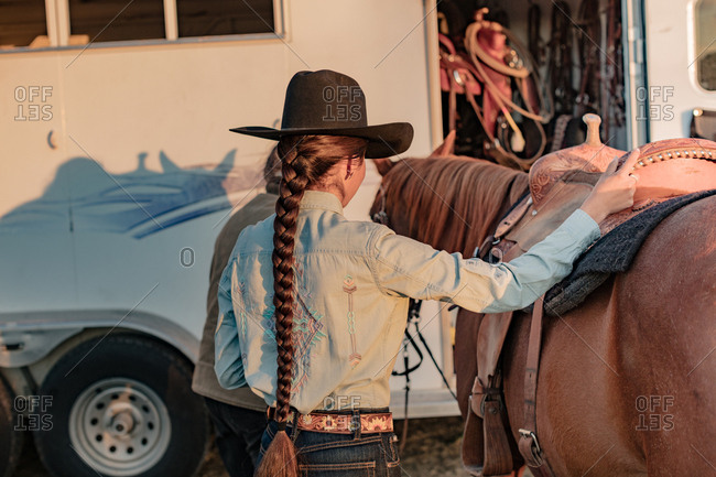 Back view of Native American young woman with long braided hair standing next to a horse