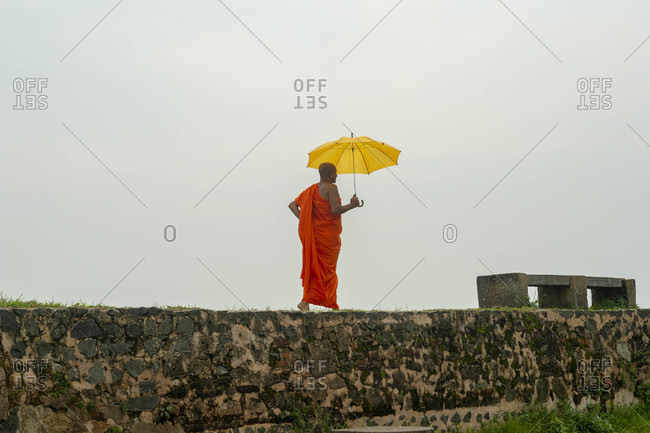 Galle, Sri Lanka - November 27, 2018: Buddhist monk walking along the fort walls past the Galle Lighthouse