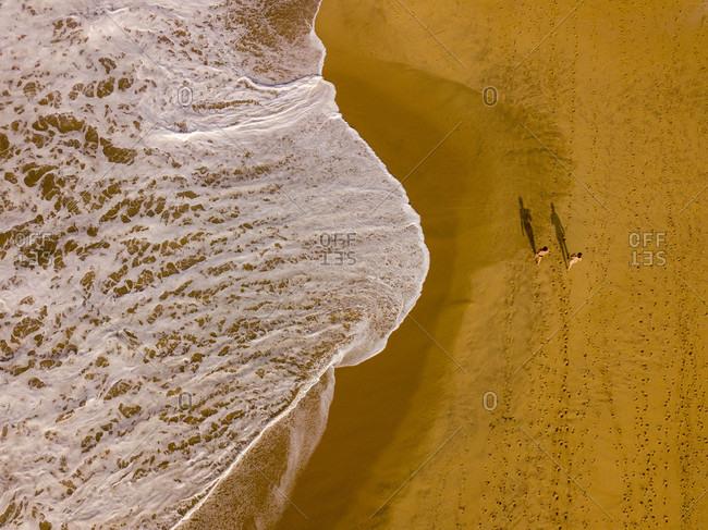 People walking along an empty beach in Hikkaduwa, Sri Lanka