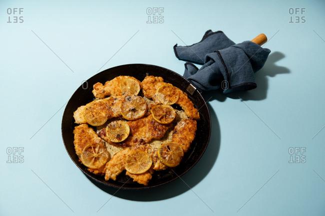Roasted chicken francese with lemon slices on blue background