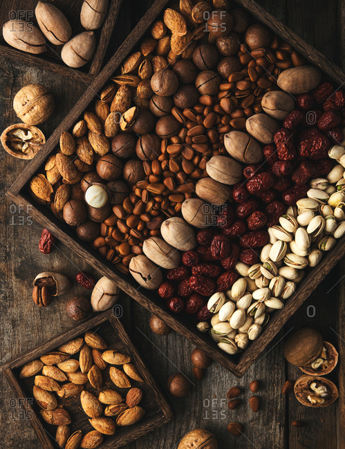 Variety of whole nuts arranged in rustic boxes on wooden table