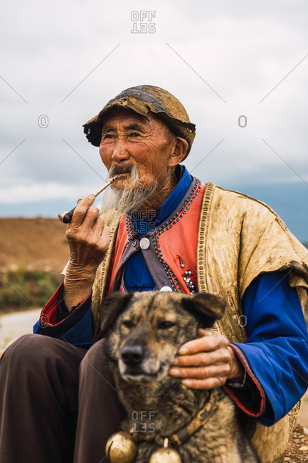 DONGCHUAN RED, YUNNAN, CHINA - JUNE 14, 2018: Relaxed senior male in bright traditional clothes sitting on ground smoking wooden tobacco pipe and petting dog sitting nearby looking away on blurred background of Dongchuan red lands in Chinese province of Yunnan
