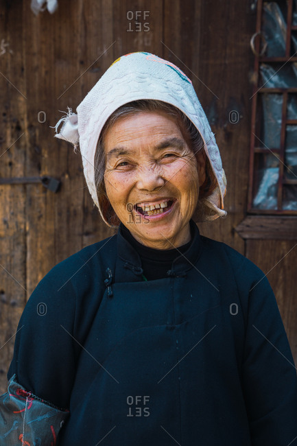 GUINZHOU, CHINA - JUNE 14, 2018: Cheerful senior villager female of Miao ethnic group in simple dark dress and white cap standing at wooden wall of house and looking at camera smiling in Guizhou province of China