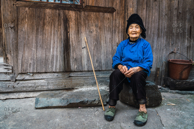 GUINZHOU, CHINA - JUNE 14, 2018: Elderly female of Miao ethnic minority in blue and black clothes and cap resting at wooden wall sitting on stone with walking cane nearby looking at camera and smiling in Guizhou province of China
