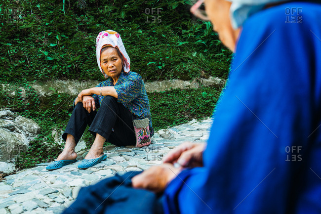 GUINZHOU, CHINA - JUNE 14, 2018: Crop side view of aged Chinese female in glasses and traditional blue clothes and cap stitching cloth in hands and looking away sitting on stones with other woman of Miao ethnic group and trees on blurred background in Guizhou, China