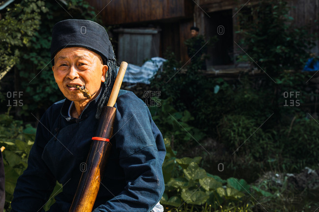 GUINZHOU, CHINA - JUNE 14, 2018: Happy elderly male of Miao ethnic minority resting outdoors on sunny summer day sitting with musical instrument and smoking rustic tobacco pipe looking away on blurred background of Chinese province of Guizhou