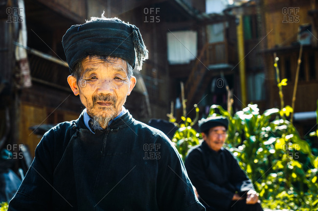 GUINZHOU, CHINA - JUNE 14, 2018: Cheerful aged male in dark clothes standing in Guizhou province