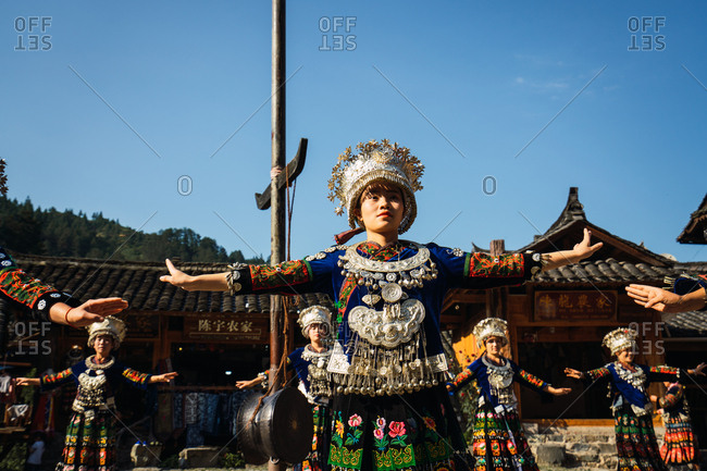 GUINZHOU, CHINA - JUNE 14, 2018: Females of Miao ethnic group in bright costumes with colorful ornaments and headdresses performing traditional festival dance on village square on sunny summer day in Guizhou province of China