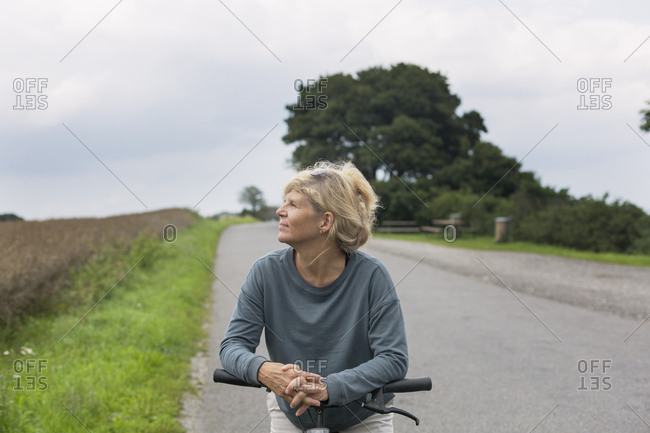 Mature woman riding a bicycle in the countryside