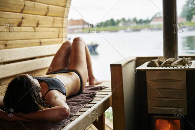 Mid adult woman lying in a sauna in Copenhagen, Denmark