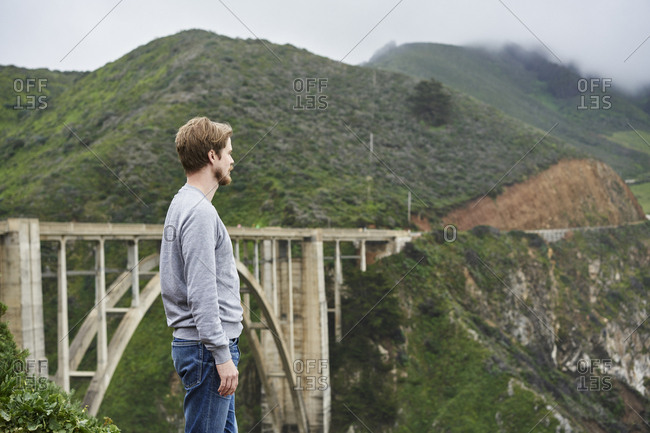 Man standing in front of bridge and mountains at Big Sur in California, USA