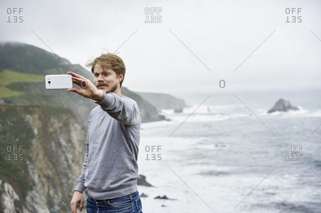 Man taking selfie at Big Sur in California, USA